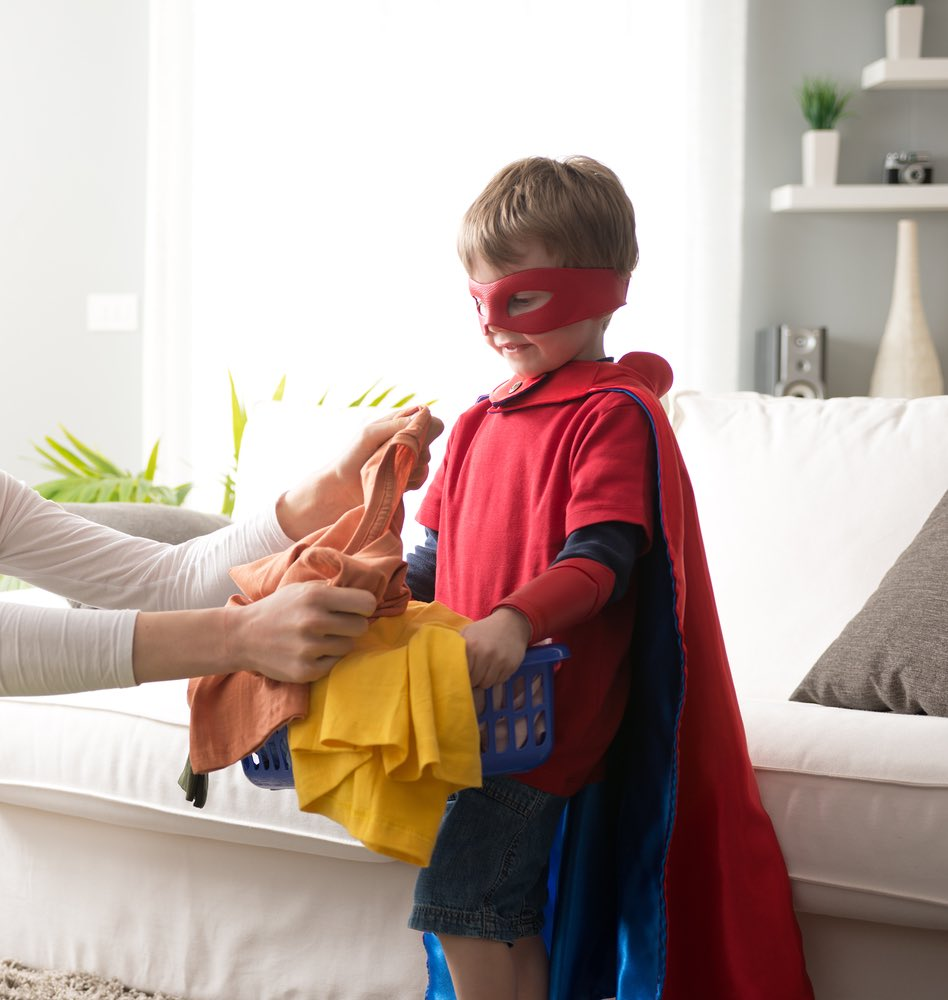Boy with superpower cape helping with laundry