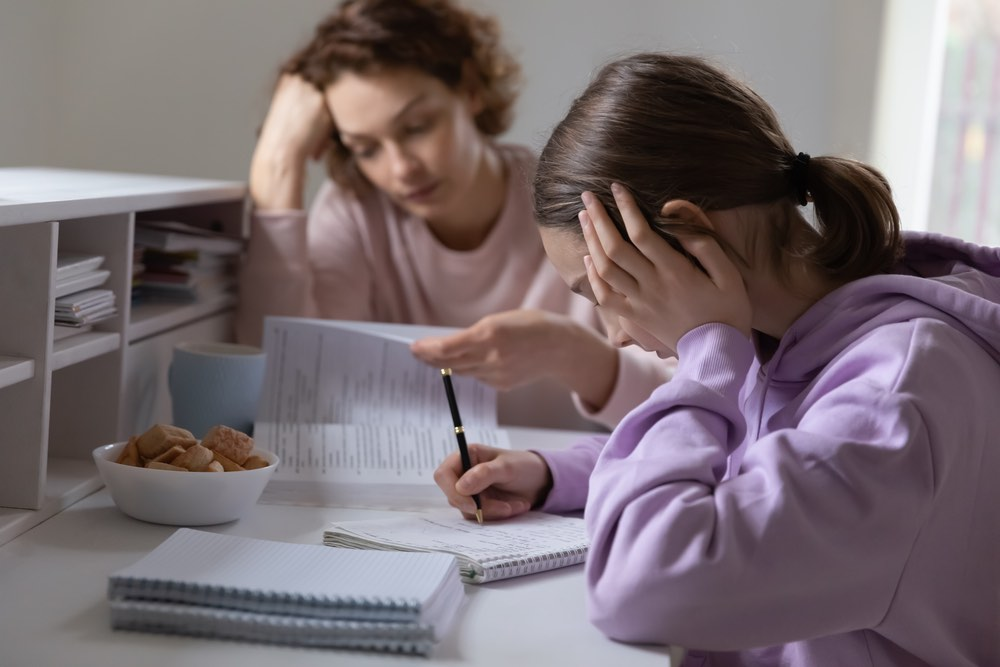 Frustrated Teen Studying Mom in Background