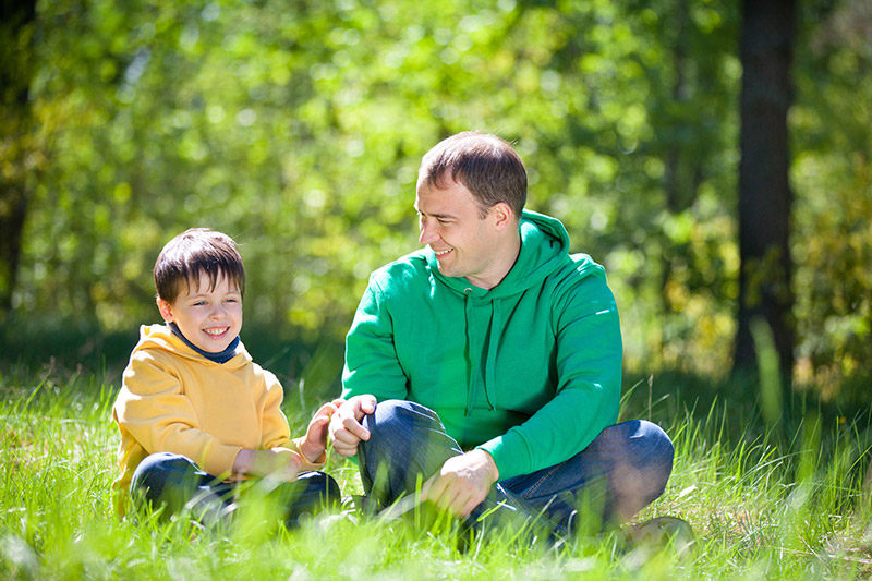 Father and Young Son Talk Outside on Grass